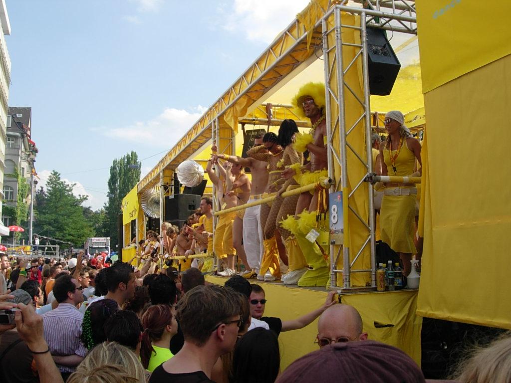 Abbildung 1 zeigt einen Musikwagen mit tanzenden Menschen auf der Street Parade 2004 in Zürich. Bild: SaMsX, gemeinfrei.