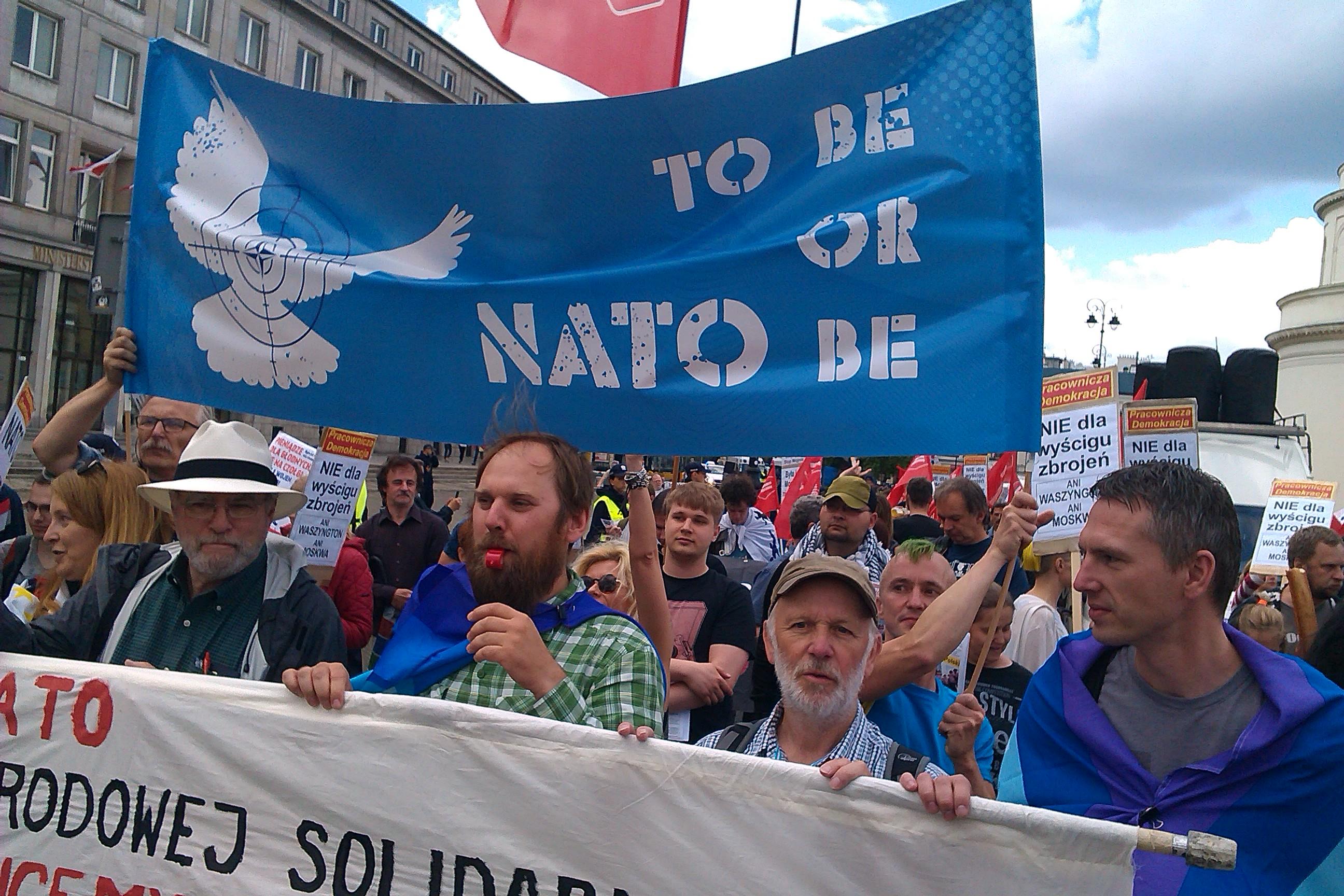"""Abbildung 2 zeigt das Banner """"To be or NATO be"""" auf einer Demonstration anlässlich des NATO-Gipfels im Juli 2016 in Warschau. Grafik des Banners: Doro Tops."""