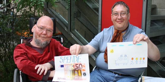 Matthias Vernaldi nimmt die 50 Euro und das Kunstwerk von Christian Specht im Garten des taz.cafés entgegen.