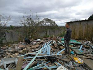 Mann auf den Trümmern eines zerstörten Hauses.