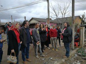 Menschen vor zerstörten Häusern in der Vila Nazaré
