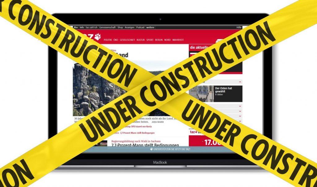 Ein Laptop mit der taz-Webseite und einem Baustellenband davor