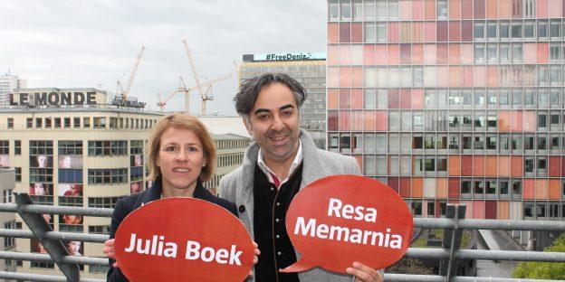 Moderatorin Julia Boek (links) und Referent Resa Memarnia. Im Hintergrund prangt der Schriftzug FreeDeniz auf dem Axe-Springer-Haus