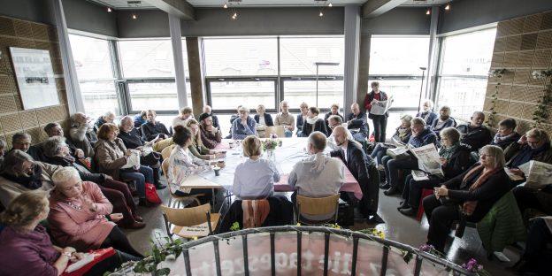 Etwa 80 Menschen sitzen im Pavillion. In der Mitte: Ein Tisch, an dem die taz.meinland-RedakteurInnen sitzen.