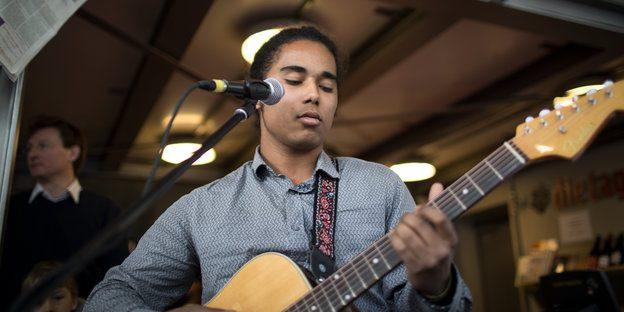 Ein junger Mann spielt eine Gitarre